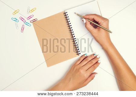 Female Hand With Pencil. White Sheet Of Paper On Desk. Notebook. Top View Of Work Desk. Mockup For Y