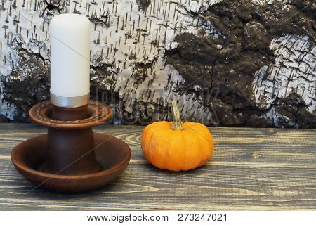 Exclusive Clay Candlestick With White Wax Candle And Decorative Orange Pumpkin Against The Backgroun