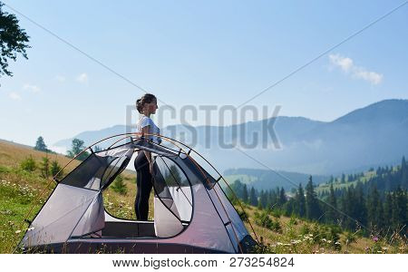 Young Slim Hiker Woman Standing At Small Tourist Tent Enjoying Beautiful Panorama Of Mountains Cover