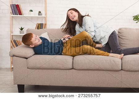 Remote Control Fight. Siblings Struggling For Television On Sofa