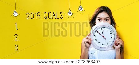 2019 Goals With Young Woman Holding A Clock Showing Nearly 12