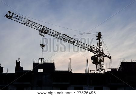 Construction of a high-rise building with a crane. Building construction using formwork. The construction crane and the building against the blue sky. poster