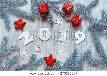 New Year 2019 background with 2019 figures, Christmas toys, blue fir tree branches and snowflakes. New Year 2019 festive seasonal design