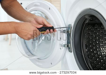 Young Handyman Fixing Washing Machine, Closeup. Laundry Day