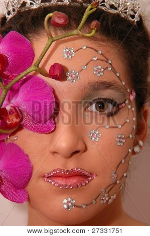 Girl wearing makeup made of rhinestone flowers with a pink orchid
