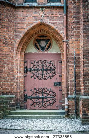 Wooden Lancet Door With Iron Forged Hinges In Wall Of Red Bricks. Garrison Church Of Our Lady Queen