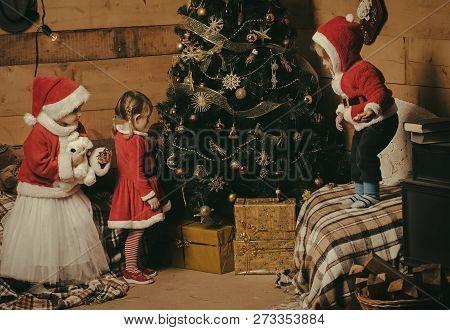 Santa Claus Kid At Christmas Tree. Winter Holiday And Vacation. Xmas Party Celebration, Childhood Ne