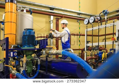 Technician On Power Industrial Plant. Engineer Operate Valve For Industrial Oil Pump System At Stati