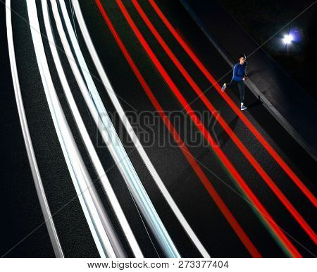Young Sports Man Running on the Night Road with Cars Light Trails. Healthy Lifestyle and Urban Active Sport Concept.
