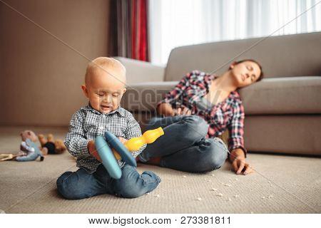 Little kid playing on the floor, mother sleeps