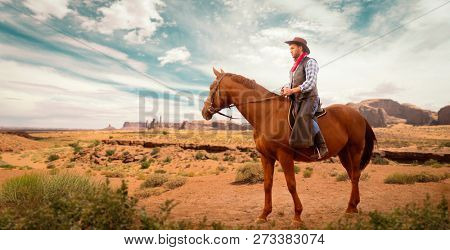 Cowboy in leather clothes riding a horse, western