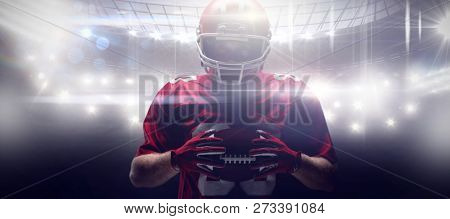American football player standing in rugby helmet and holding rugby ball against american football arena