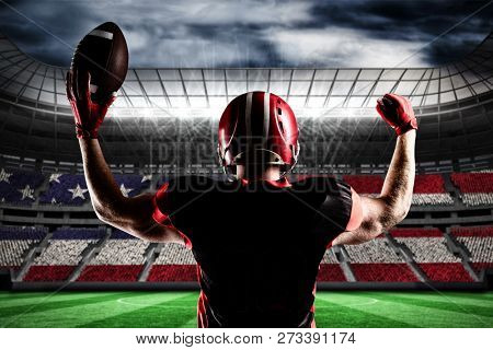 American football player standing with helmet holding football in victory against stadium full of usa football fans