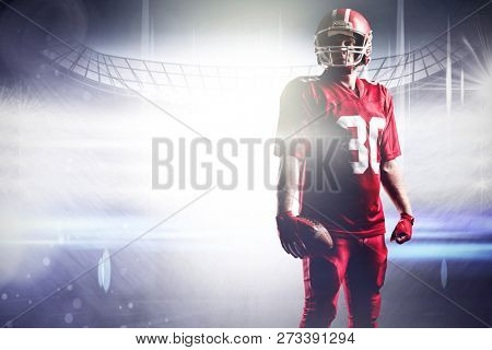 American football player in helmet holding with football against american football arena