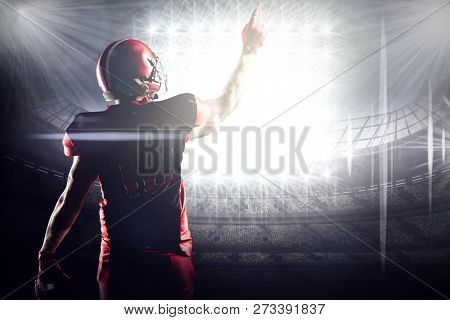 American football player in helmet pointing upwards against american football arena