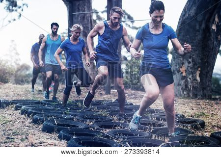 People receiving tire obstacle course training in boot camp