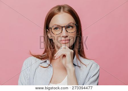 Thoughtful Business Lady Holds Chin, Looks Aside With Pensive Expression, Wears Spectacles, Has Dark