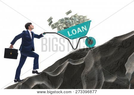 Businessman pushing wheelbarrow uphill in debt loan concept
