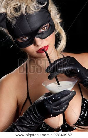 Portrait of the blonde model wearing black cat, licking - drinking milk from the martini glass poster