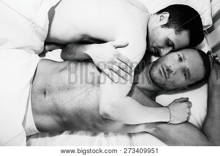 Attractive Male Gay Couple Lying Together In Bed, One Kissing Other Looking At Camera