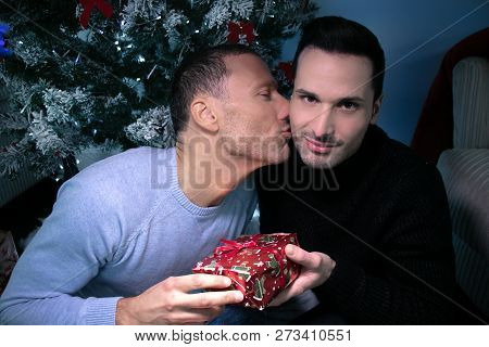 Gay Male Couple Exchanging Christmas Gift In Front Of Tree. One Kissing, Other Smiling At Camera