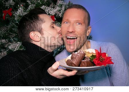 Male Gay Couple Kissing And Laughing In Front Of Christmas Tree With Plate Of Cakes