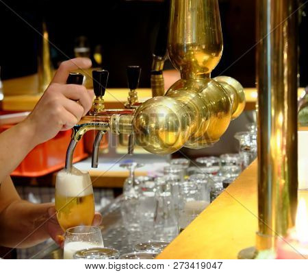 Female bartender pouring a beer in tap.