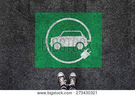 A Man With A Shoes Is Standing Next To Electric Car Sign On Road Asphalt