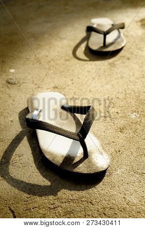 Dirty Old Slippers At On Cement Background