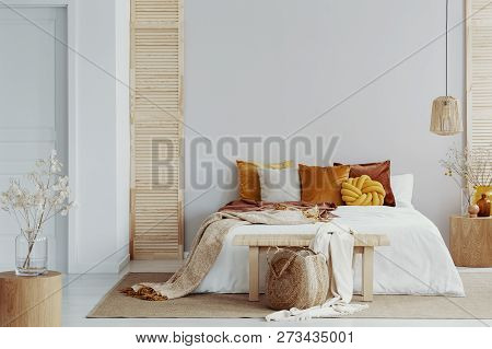 Brown And Orange Pillows On White Bed In Natural Bedroom Interior With Wicker Lamp And Wooden Bedsid