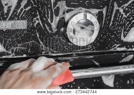 Cleaning in the kitchen, female hand washes the black glass surface of the built-in oven, soapy foam is visible. poster
