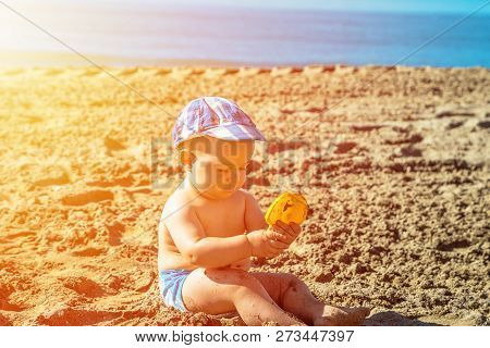 Baby Boy Playing On The Beach At The Summer Day Time.