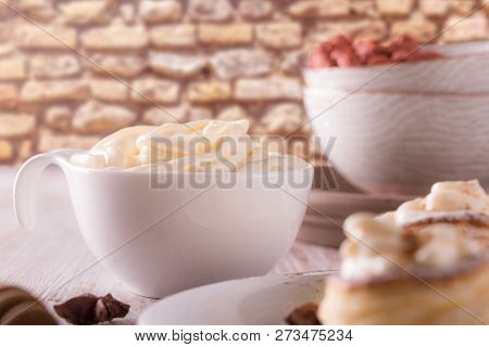 White Cup Full Of Sweet Curd Cheese On Wooden Board