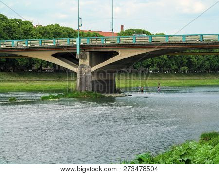Tomas Masaryk Bridge in Uzhhorod close-up and people wade the river ford under it. The urban landscape of Uzhgorod with the shallow river Uzh and the Great Bridge in spring-summer day poster