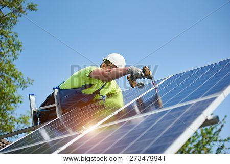 Technician Connecting Solar Photo Voltaic Panel To Metal Platform Using Screwdriver Standing On Ladd