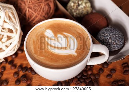 Close-up Of A Cup Of Latte Or Cappuccino With Latte Art. Coffee And Cakes On A Wooden Table With Sca