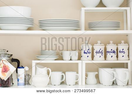 Kitchen Cupboard, White Porcelain Dishes, Tea Pot, Mugs And Cups.