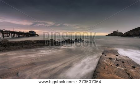 Dawn And A Long Exposure At High Tide Over Mumbles Pier And Mumbles Lighthouse In Swansea, South Wal