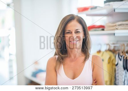 Beautiful middle age hispanic woman standing with smile on face at clothes store. Shop owner and shop assistant smiling confident and cheerful with crossed arms.