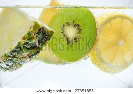 Slices Of Fresh Pineapple, Lemon And Kiwi In Clear Clear Water.