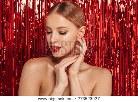 Beauty portrait of a pretty young topless woman standing isolated over red sparkling background poster