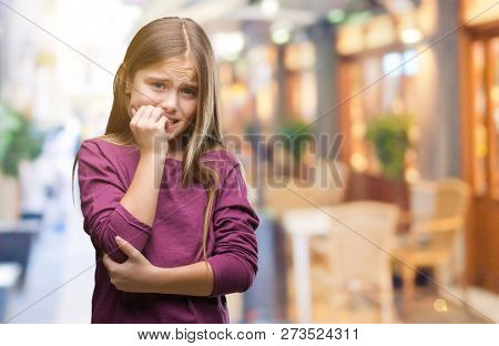 Young beautiful girl over isolated background looking stressed and nervous with hands on mouth biting nails. Anxiety problem.