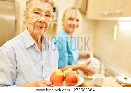 Senior woman with fruit and a nursing woman in the kitchen of senior citizen apartment