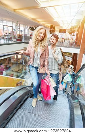 Smiling young couple together on the escalator in shopping mall