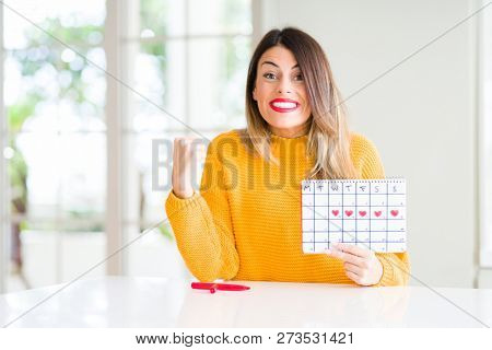 Young beautiful woman holding menstruation calendar at home screaming proud and celebrating victory and success very excited, cheering emotion