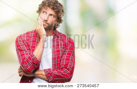 Handsome hispanic model man over isolated background with hand on chin thinking about question, pensive expression. Smiling with thoughtful face. Doubt concept.