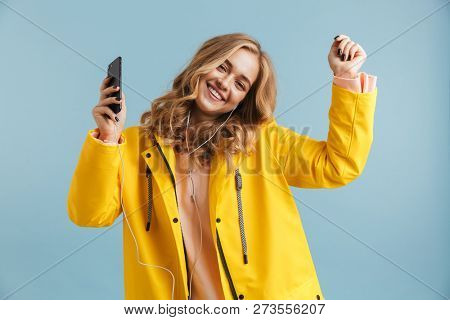 Image of positive woman 20s wearing yellow raincoat holding mobile phone and listening to music via earphones isolated over blue background