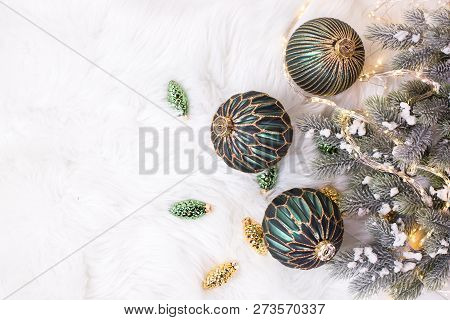 Border From Green And Golden Balls, Golden Pine Cones, Fairy Lights  And Fir Tree Branches  On White