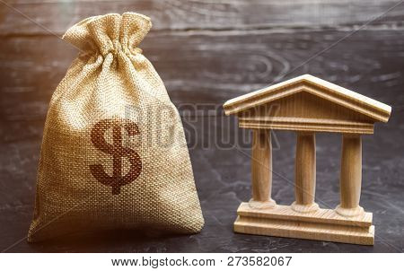 A Bag With Dollar Money And A Bank Or Government Building. Deposits, Investment In The Budget. Grant