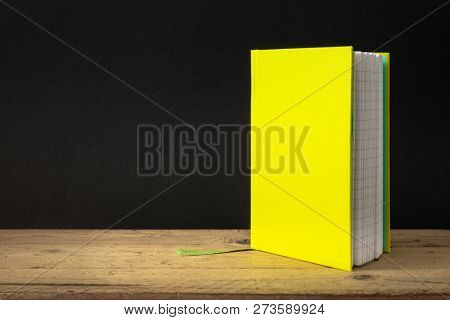 An image of a yellow green note book on a wooden table